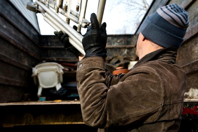 Junk Removal worker filling metal trash in bin